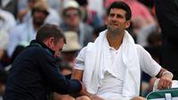 Petenis Serbia, Novak Djokovic mendapat perawatan medis saat melawan petenis Ceko, Tomas Berdych pada babak perempatfinal Wimbledon 2017, Rabu (12/7). Juara Wimbledon tiga kali itu gagal melanjutkan laga lantara cedera. (Gareth Fuller/PA via AP)