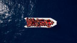 Pengungsi dan imigran mengenakan pelampung saat diselamatkan oleh LSM Proactiva Open Arms Spanyol di utara pantai Libya, Minggu (6/5). Mereka meninggalkan Libya dan mencoba mencapai Eropa. (AP Photo/Felipe Dana)
