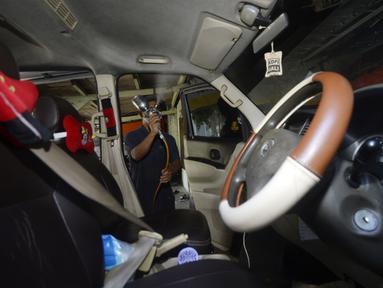 Pekerja menyemprotkan cairan disinfektan ke taksi online yang akan melakukan servis di Bengkel Yoyo, Pamulang, Tangerang Selatan, Banten, Rabu (2/4/2020). Penyemprotan disinfektan dilakukan untuk mengantisipasi  penyebaran virus corona COVID-19 antarpenumpang. (merdeka.com/Dwi Narwoko)