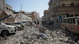 Petugas keamanan setempat memeriksa di sekitar lokasi terjadi serangan udara di kompleks kepresidenan, di Sanaa, Yaman (7/5). (AP Photo/Hani Mohammed)
