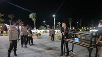 Pekerja salah satu cafe di pusat keramaian di Citraland Baywalk, Kelurahan Tondo, Kota Palu mengangkat meja untuk menutup cafe setelah petugas gabungan mendatangi lokasi itu, Kamis malam (31/12/2020). (Foto: Heri Susanto/ Liputan6.com).