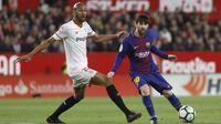 Pemain Barcelona, Lionel Messi (kanan) mengecoh pemain Sevilla, N'zonzi pada laga La Liga Santander di Sanchez Pizjuan stadium, (31/3/2018). Barcelona bermain imbang 2-2 dengan Sevilla. (AP/Miguel Morenatti)