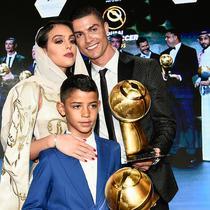 Striker Juventus, Cristiano Ronaldo bersama kekasihnya Georgina Rodriguez dan putranya Cristiano Jr berpose dengan trofi Pemain Terbaik Tahun 2018 selama Dubai Globe Soccer Awards ke-10 di Dubai (3/1). (AFP Photo/Fabio Ferrari)