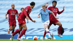 Gelandang Manchester City, Kevin De Bruyne, berusaha melewati bek Liverpool, Virgil Van Dijk, pada laga lanjutan Premier League pekan ke-32 di Stadion Etihad, Jumat (3/7/2020) dini hari WIB. Manchester City menang 4-0 atas Liverpool. (AFP/Dave Thompson/pool)
