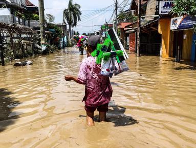 Pedagang alat kebersihan menerobos banjir di kompleks Pondok Gede Permai, Jatiasih, Bekasi, Jumat (22/4). Mereka menjajakan dagangannya berupa alat kebersihan ketika banjir di  kawasan tersebut mulai surut. (Liputan6.com/Fery Pradolo)