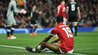Striker Manchester United, Marcus Rashford duduk di lapangan setelah gagal mencetak gol ke gawang Sevilla pada laga leg kedua 16 besar Liga Champions di Old Trafford, Selasa (13/3). Manchester United menyerah 1-2 kepada tamunya Sevilla. (Oli SCARFF/AFP)