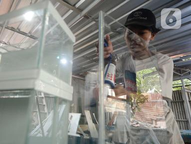 Perajin menyelesaikan pesanan akuarium ikan hias dari kaca di Pamulang, Tangerang Selatan, Selasa (21/07/2020). Pesanan akuarium dari Tangerang Selatan dan sekitarnya di saat kondisi pandemi corona Covid-19 ini meningkat hingga 100 persen. (merdeka.com/Dwi Narwoko)