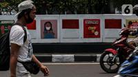 Warga melintasi mural sosialisasi bahaya COVID-19 di Jalan Sultan Iskandar Muda, Jakarta, Rabu (23/9/2020). PSBB pengetatan sepekan terakhir ini belum efektif menurunkan angka jumlah harian Covid-19 di DKI yang tercatat bertambah 1.122 kasus di ibu kota pada Selasa (22/9). (Liputan6.com/Johan Tallo)