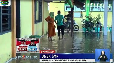 Demi lancarnya UNBK, guru memasang beton di pintu ruang kelas pada Rabu malam saat hujan deras mengguyur.