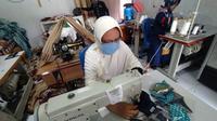 Salah satu karyawan Bumdes Timur Harapan, Desa Ayula Timur saat membuat masker kain (Foto: Arfandi Ibrahim/Liputan6.com)