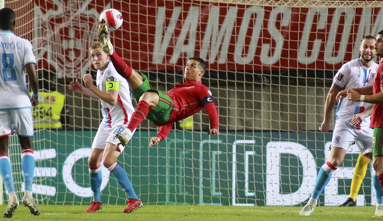 Penyerang Portugal Cristiano Ronaldo (tengah) mencoba mencetak gol dengan tendangan overhead ke gawang Luksemburg pada lanjutan Kualifikasi Piala Dunia 2022 di Stadion Do Algarve, Rabu (13/10/2021) dini hari WIB. Hat-trick Ronaldo membuat Portugal menang 5-0 atas Luksemburg. (AP Photo/Joao Matos)