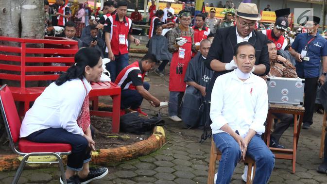 Presiden Joko Widodo disaksikan Ibu Negara Iriana bersiap mengikuti cukur rambut massal di Garut, Jawa Barat, Sabtu (19/1). Dalam acara cukur rambut massal ini, rambut Jokowi dicukur oleh tukang cukur langganannya, Herman. (Liputan6.com/Angga Yuniar)