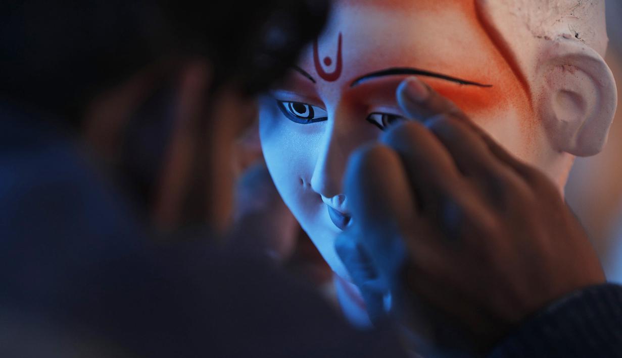 Pematung Nepal Ravi Pandit memberikan sentuhan akhir pada patung dewi Hindu Durga menjelang festival Dashain di Kathmandu, Nepal (14/10/2020). Keluarga Pandit akan menjual setidaknya 200 patung untuk festival ini, tetapi tahun ini hanya menjual 20 patung karena pandemi. (AP Photo/Niranjan Shrestha)