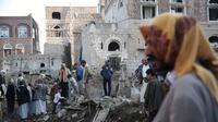 Warga berada di puing-puing sejumlah rumah yang dihantam koalisi Arab Saudi di dekat komplek Kementerian Pertahanan Yaman di Sanaa (11/11/2017). (AP Photo/Hani Mohammed)
