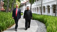 Pemandangan saat Presiden AS Donald Trump (kiri) dan Pemimpin Korea Utara Kim Jong-un berjalan di taman Hotel Capella, Pulau Sentosa, Singapura, Selasa (12/6). Kegiatan ini dilakukan saat istirahat pembicaraan antara AS-Korut. (Anthony Wallace/Pool/AFP)