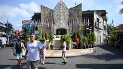 Turis asing mengunjungi Monumen Bom Bali di Kuta, dekat Denpasar pada Sabtu (12/10/2019). MeMperingati 18 tahun peristiwa bom Bali yang terjadi pada 12 Oktober 2002, wisatawan dan kerabat korban mengunjungi tugu peringatan untuk berdoa dan tabur bunga. (SONNY TUMBELAKA / AFP)