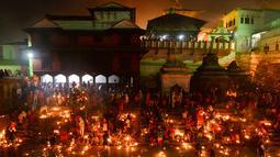 Umat Hindu Nepal mengarungi lampu minyak selama festival Bala Chaturdashi di Kuil Pashupatinath di Kathmandu (6/12). Festival Bala Chaturdashi ini dirayakan untuk mengenang anggota keluarga yang telah tiada. (AFP Photo/Prakash Mathema)