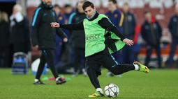 Penyerang Barcelona, Lionel Messi menendang bola saat sesi latihan di Emirates Stadium, Inggris, (23/2). Barcelona akan bertanding melawan Arsenal di leg pertama 16 besar Liga Champions. (Reuters/Matius Childs)