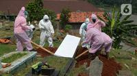 Petugas pemulasaraan jenazah Covid-19 memakamkan jenazah yang meninggal ketika menjalani isolasi mandiri di Kampung Gedong, Jakarta, Sabtu (10/7/2021). Proses pemulasaran jenazah dilakukan sesuai prokes Covid-19 dikarenakan hasil test swab korban positif. (merdeka.com/Imam Buhori)