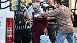 Seorang imigran wanita bersiap naik bus selama operasi polisi di pusat Athena, Yunani (19/9/2019). Pembersihan para imigran di pusat kota tersebut digerakkan oleh pemerintah konservatif yang baru. (AFP Photo/Louisa Gouliamaki)