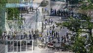Para pengunjuk rasa, seperti yang terlihat melalui jendela, mengambil bagian dalam demonstrasi menentang kudeta militer di Yangon 28/2/2021).  Myanmar berada dalam kekacauan sejak tentara merebut kekuasaan dan menahan pemimpin pemerintah terpilih Aung San Suu Kyi. (AFP/ Ye Aung Thu)