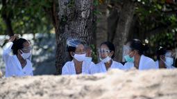Umat Hindu mengenakan face shield menghadiri upacara Melasti menjelang Hari Raya Nyepi di Pantai Kuta, Bali (11/3/2021). Upacara Melasti dilakukan oleh perwakilan desa adat dengan jumlah terbatas serta menerapkan protokol kesehatan untuk mencegah penyebaran pandemi COVID-19. (AFP/Sonny Tumbelaka)