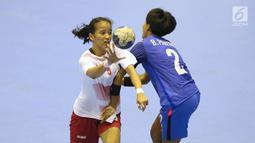 Pemain bola tangan putri Indonesia, Lia Apriliani (kiri) mencoba melewati adangan pemain Thailand, Pawinee Bunjarern pada babak penyisihan grup B Asian Games 2018 di Jakarta, Kamis (16/8). Indonesia kalah 16-34. (Liputan6.com/Helmi Fithriansyah)