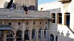 Dua pemuda melompat berlatih parkour di Aleppo, Suriah, (7/4). Setelah pemerintah Suriah mengambil alih kendali penuh Aleppo dari pasukan pemberontak Desember 2016, beberapa pemuda kini menyalurkan hobinya, yaitu parkour.  (AFP Photo/George Ourfalian)