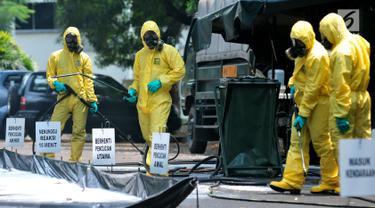 Tim Pasukan Gerak Cepat (PGC) melakukan sterilisasi sebuah mobil yang kedapatan positif terjangkit pandemi influenza H7N9 saat simulasi penanganan Episenter Pandemi Influenza di Puspiptek Tangerang Selatan, Rabu (20/9). (Liputan6.com/Helmi Afandi)