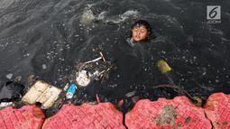 Seorang anak berenang di antara sampah di Kanal Banjir Barat (KBB), Petamburan, Jakarta, Senin (12/8/2019). Surutnya debit air KBB akibat musim kemarau dimanfaatkan anak-anak untuk bermain sambil mencari ikan. (Liputan6.com/Fery Pradolo)