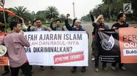 Sejumlah massa yang tergabung dalam Gerakan Mahasiswa Pembebasan (GMP) membentangkan spanduk saat menggelar aksi unjuk rasa Silang Monas, Jakarta, Rabu (12/7). Dalam aksinya mereka menolak Perppu pembubaran Ormas Islam. (Liputan6.com/Faizal Fanani)