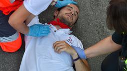 Petugas medis menolong salah seoarang peserta yang keseruduk banteng selama hari ketiga Festival San Fermin di Pamplona, Spanyol utara, (9/7). (AFP Photo/Ander Gillenea)