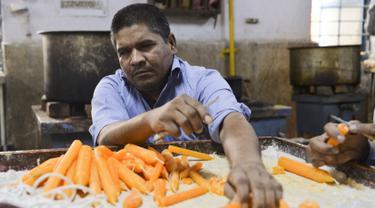 Pekerja tunanetra membuat lilin di bengkel Blind School Relief Association, New Delhi, India, Rabu (16/10/2019). Perkumpulan tersebut menjual lilin, lampu minyak, dan produk kertas yang dibuat oleh para pekerja tunanetra jelang Festival Diwali atau Festival Cahaya. (Sajjad HUSSAIN/AFP)