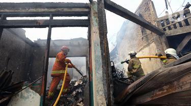 Petugas pemadam kebakaran melakukan pendinginan rumah dan kios yang terbakar di Jalan Minangkabau, Jakarta, Selasa (7/7/2020). Delapan unit mobil pemadam kebakaran dikerahkan untuk memadamkan api yang hingga saat ini belum diketahui penyebab kebakaran. (merdeka.com/Imam Buhori)