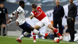 Bek Arsenal, Kieran Tierney berusaha melewati bek Tottenham Hotspur, Serge Aurier pada pertandingan lanjutan Liga Inggris di Stadion Tottenham Hotspur di London, Inggris, Minggu (12/7/2020). Tottenham menang tipis atas Arsenal 2-1. (Tim Goode/Pool via AP)