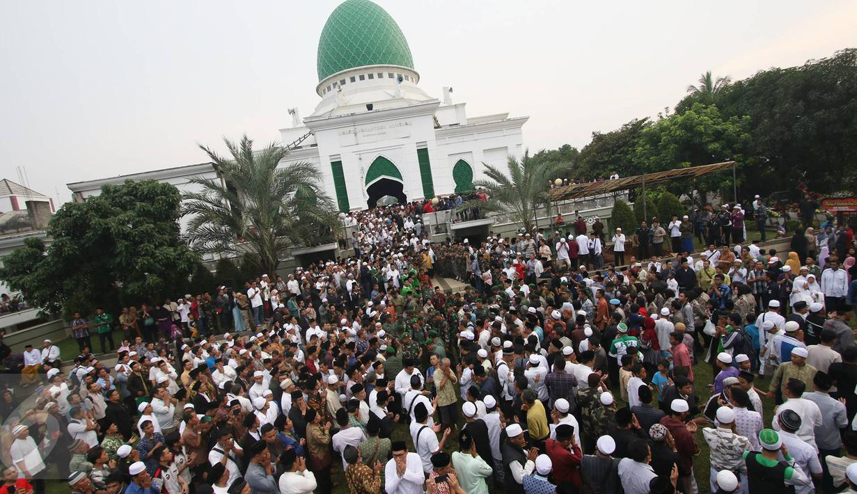 Ribuan pelayat mengantarkan jenazah tokoh PBNU KH Hasyim Muzadi ke pemakaman di Pondok Pesantren Al Hikam, Beji, Depok, Kamis (16/3). Jenazah KH Hasyim Muzadi dimakamkan secara militer dengan iringan lantunan tahlil. (Liputan6.com/Immanuel Antonius)