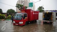 Mobil pompa penyedot air Dinas Tata Air dikerahkan untuk menyedot air banjir yang merendam Jalan Gunung Sahari, Jakarta, Selasa (21/2). Hujan yang mengguyur sejak Selasa dinihari membuat sebagian wilayah di Jakarta banjir. (Liputan6.com/Faizal Fanani)