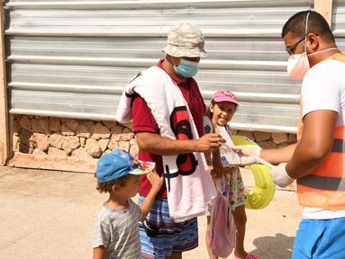 Petugas kesehatan membagikan masker kepada seorang pria di sebuah pantai di Rabat, Maroko, 27 Agustus 2020. Maroko pada 27 Agustus 2020 melaporkan 1.221 kasus baru COVID-19, menambah jumlah kasus infeksi di negara itu sejak 2 Maret menjadi 57.085. (Xinhua/Chadi)