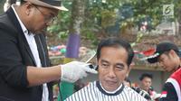 Presiden Joko Widodo saat mengikuti acara cukur rambut massal di Garut, Jawa Barat, Sabtu (19/1). Tak hanya Jokowi, Menteri PUPR Basuki Hadimuljono serta Kepala Sekretariat Presiden Heru Budi Hartono  ikut memangkas rambutnya. (Liputan6.com/Angga Yuniar)