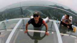 Seorang pria berpose saat mengunjungi platform kaca di Shilin Gorge, Beijing, Cina, (27/5). Objek wisata baru di China ini berada di ketinggian 768 meter dan berjarak 400 meter dari dasar jurang. (REUTERS/Kim Kyung-Hoon)