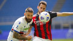 Pemain AC Milan, Hakan Calhanoglu, berebut bola dengan pemain Sampdoria, Lorenzo Tonelli, pada laga Liga Italia di Stadion San Siro, Minggu (4/4/2021). Kedua tim bermain imbang 1-1. (AP Photo/Antonio Calanni)