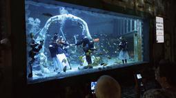 Anggota keluarga menonton Lisa Huggins dan Chris Jackson selama upacara pernikahan bawah air mereka di Bear Grylls Adventure, Inggris, Rabu (8/9/2021). Penggemar menyelam itu berencana akan menikah di luar negeri tetapi gagal akibat Covid-19, dan mencari alternatif yang unik. (Jacob King/PA via AP)
