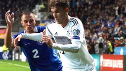 Bek Estonia Gert Kams (kiri) berusaha merebut bola yang dibawa striker Jerman, Luca Waldschmidt pada pertandingan grup C kualifikasi Euro 2020 di Tallinn, Estonia (13/10/2019). Jerman menang telak 0-3 atas Estonia. (AFP Photo/Janek Skarzynski)