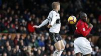 Striker Manchester United, Romelu Lukaku, duel udara dengan bek Fulham, Maxime Le Marchand, pada laga Premier League di Stadion Craven Cottage, London, Sabtu (9/2). Fulham kalah 0-3 dari MU. (AFP/Ian Kington)