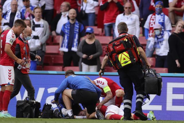 Gelandang Denmark, Christian Eriksen tergeletak di tanah setelah pingsan pada laga Denmark vs Finlandia di Grup B Euro 2020 di Parken Stadium, Copenhagen, Sabtu (12/6/2021). Eriksen tiba-tiba terjatuh dan kehilangan kesadaran saat hendak menyambut lemparan ke dalam. (Friedemann Vogel/Pool via AP)