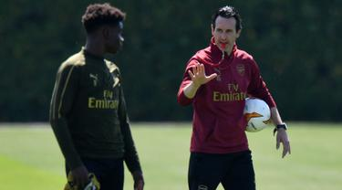 Pelatih Arsenal, Unai Emery (kanan) berbincang dengan pemainya selama sesi pelatihan tim di pusat pelatihan London Colney di St. Albans (21/5/2019). Arsenal akan bertanding melawan Chelsea pada babak Final Liga Europa pada 29  Mei di Baki Olimpiya Stadionu. (AFP Photo/Olly Greenwood)