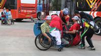 Salah satu volunteer Asian Para Games 2018 membantu menaikkan pengunjung ke kendaraan khusus difabel di dekat pintu utama GBK, Jakarta, Kamis (11/10). Mereka bertugas membantu kelancaran Asian Para Games 2018. (Liputan6.com/Helmi Fithriansyah)
