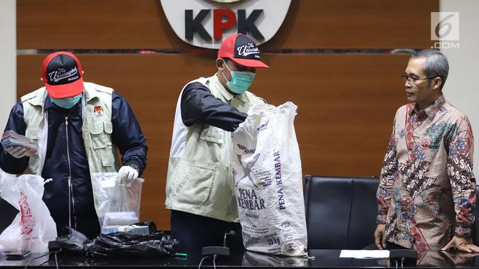 Petugas KPK mengambil barang bukti uang saat jumpa pers terkait OTT Bupati Cirebon Sunjaya Purwadi Sastra di Jakarta, Kamis (25/10). Selain jual beli jabatan, Sunjaya juga menjadi tersangka atas proyek dan perizinan. (Liputan6.com/Herman Zakharia)