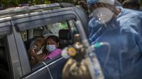 Seorang pasien menerima oksigen di dalam mobil yang disediakan oleh Gurdwara, tempat ibadah Sikh, di New Delhi, 24 April 2021. Banyak kota di India kewalahan oleh pasien yang mengakibatkan kekurangan tempat tidur rumah sakit dan oksigen yang menyebabkan ribuan kematian. (AP Photo/Rajesh Kumar Singh)