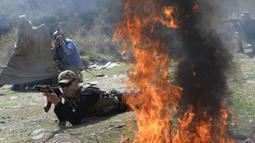 Api berkobar saat pasukan ikut serta dalam latihan gabungan Kyrgyzstan dan India di Ngarai Tatyr, selatan Bishkek, dekat Desa Arashan, Kyrgyzstan, Senin (26/4/2021). Pasukan tersebut berlatih untuk mengoordinasikan aksi mereka melawan militan. (AP Photo/Vladimir Voronin)